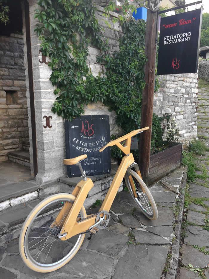 """Για μία μέρα πάρκαρε το ξύλινο ποδήλατο τού Paul Ευμορφίδη """"στου Τάκη"""" πριν αναχωρήσει για το οδοιπορικό του προς τα Τίρανα. Ο Paul Ευμορφίδης καθ' οδόν προς την Αλβανία σε ένα ποδηλατικό road trip σταμάτησε για ένα πιτ-στοπ στο Δίλοφο όπου και έφαγε με την παρέα του """"στου Τάκη"""" αφού διανυκτέρευσε στον Ξενώνα """"Αρχοντικό τού Διλόφου""""."""